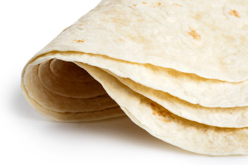 Detail of stack of folded tortilla wraps on white.