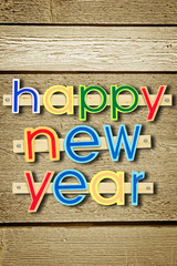 Nailed greeting text Happy New Year on wooden background