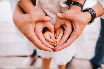 A family of hands form a heart - father on the outside, then mother's hands and infant baby hands in the middle.
