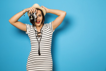 Fashion young girl makes the photo with old camera. Blue backgro