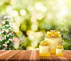 Golden presents on wood plank table top with christmas tree blur