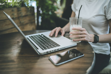 A girl sitting at a wooden table outdoors and using a laptop. On the table lies a smartphone. In a female hand smart watches. Woman holding a glass of drink. Girl uses the gadget.