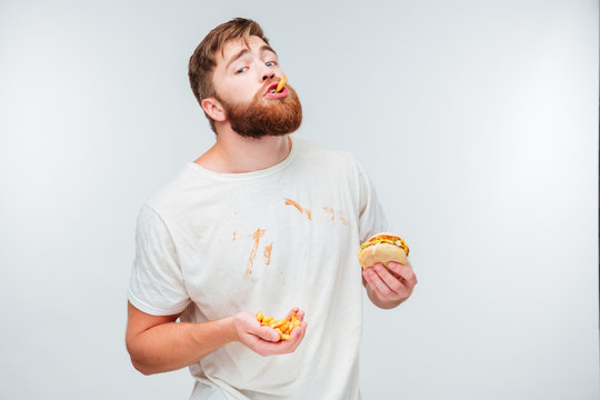 Happy bearded man enjoying eating hamburgers