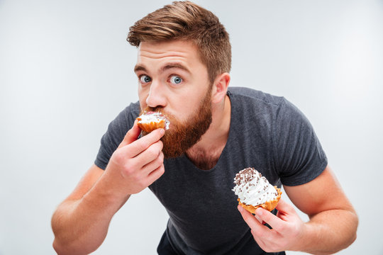 Close up portrait of a hungry man biting cream cake