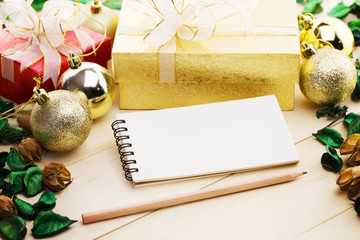Blank notepad as copy space with gift box and dried leaf on old wooden plates. Lovely holiday background.