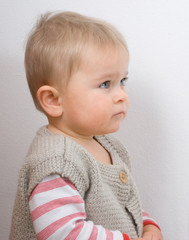 Serious one and half year old boy on a off-white wall background