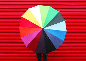 Autumn photo woman holding colorful umbrella over red background