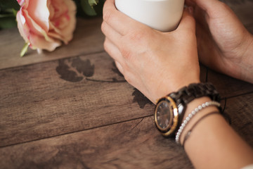 Girl is holding white cup in hands. White mug for woman, gift. Female hands with watch and bracelets holding hot cup of coffee or tea in morning. Selective focus