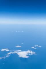 Piękny widok z samolotu na horyzont - błękitne niebo nad chmurami i ocean