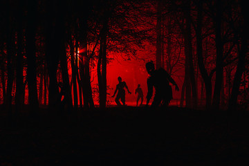 bloodthirsty zombies attacking. hungry zombies in the woods. Silhouettes of scary zombies walking in the forest at night Wall mural