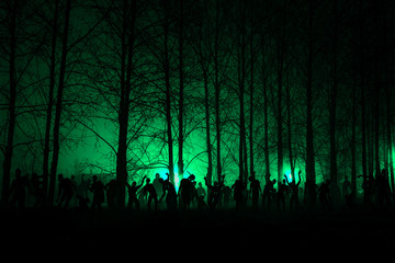 crowd of hungry zombies in the woods. Silhouettes of scary zombies walking in the forest at night. green Acid variant