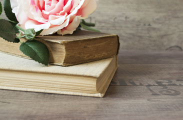 Old books and flower rose on a wooden background. Romantic floral frame background. Picture of a flowers lying on an antique book. Flowers on vintage wood background with romantic vintage background.