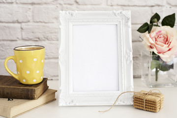 Frame Mockup. White Frame Mock Up. Yellow Cup Of Coffee With White Dots, Cappuccino, Latte, Old Books, Cookies. Vase with Flower Rose, Styled Stock Photography. Empty Frame. Leisure Lifestyle Concept.