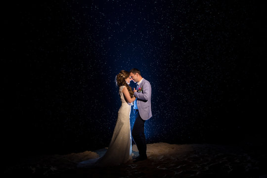 Wedding night. Happy couple, bride and groom hugging at the night wedding ceremony