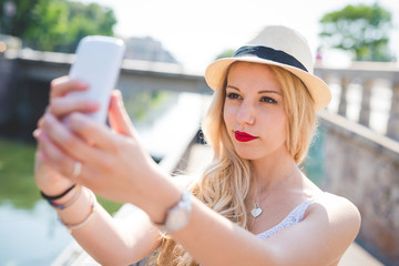 Half length of young handsome caucasian long blonde straight hair woman holding a smartphone, taking a selfie outdoor in the city - vanity, social network, happiness concept