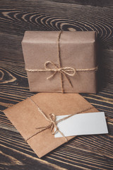Vintage gift box with blank tag on old wooden background.