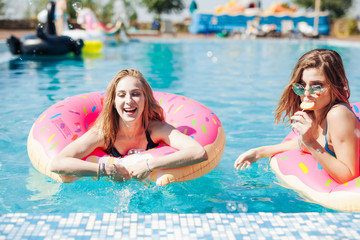 Two girls playing with water in the pool mattresses donuts