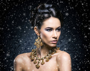 Portrait of a young woman in jewelry on snow