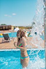 Beautiful woman having a fun while pour water fountain