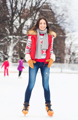 Young and pretty girl skating on outdoor ice-rink