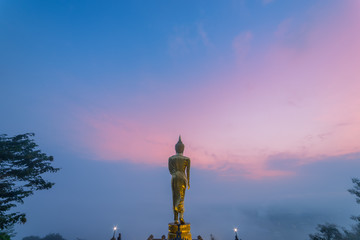 Sunrise scence of Golden Buddha statue standing on a mountain Wat Phra That Khao Noi, Nan Province, Thailand