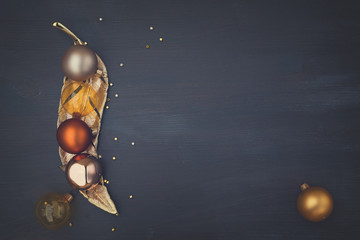 Christmas golden ball decorations on dark wooden background with copy space, retro toned