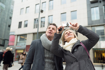 Senior couple on a walk in city centre taking picture.