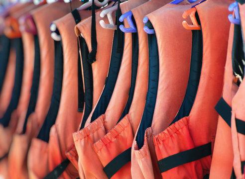 Many life jackets on the beach.