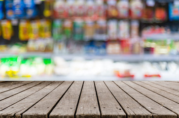 Wooden table and blurred image of shelf in supermarket