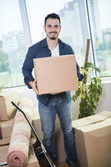 Cheerful young man holding a cardboard boxes and smiling at camera while other carton boxes laying on background