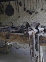 Alte Werkstatt mit Werkzeugen an der Wand und einem antiken Schraubstock