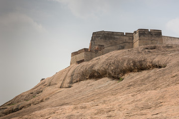 Dindigul, India - October 23, 2013: Brown-beige boulder with the ramparts of the historic Dindigul Rock fort under light blue sky. Brown-beige as dominant color.