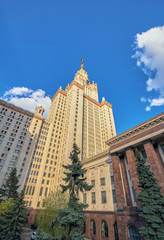 Wide angle view of tall Moscow university building with arrows of windows and golden spire under cloudy blue sky in sunny autumn