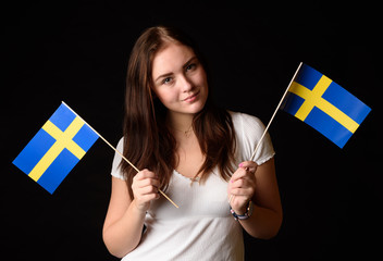 Girl with two Swedish flags isolated on black background