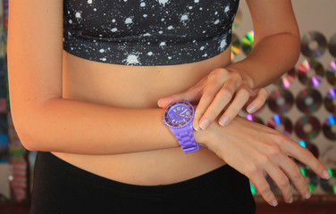 sport girl looking at her purple sport watch