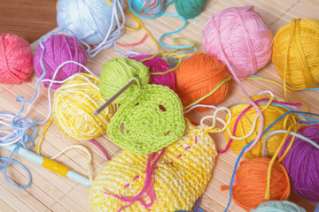 Colorful clews yarn and crochet hook on wooden background. Toned and processing photos