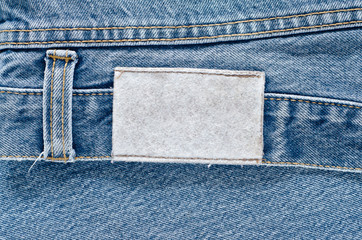 Jeans background texture,Blank real leather jeans label sewed on old worn jeans.Denim jeans texture or denim jeans background with label.Denim jeans texture or denim jeans background with old torn.