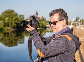 elderly man photographs the landscape
