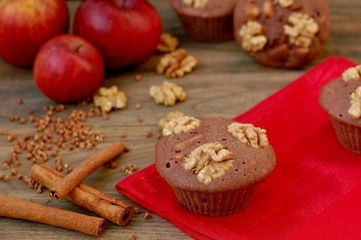 Gluten free muffins from buckwheat flour, apple, cinnamon and walnuts on red cloth on brown wooden table with black background
