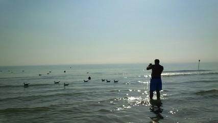 uomo che fotografa i gabbiani in mare
