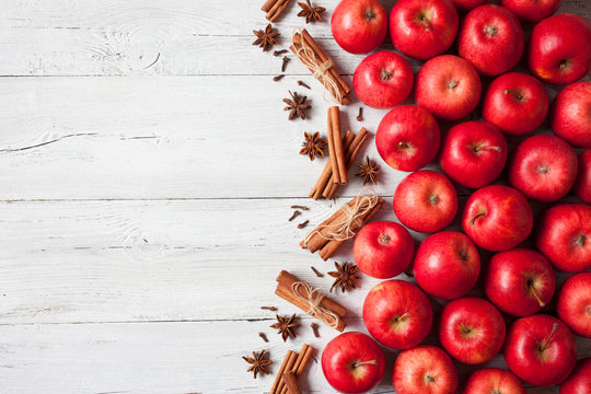 Wooden background with red apples and spices