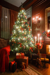 Fond de hotte en verre imprimé Montagne Christmas evening by candlelight. classic apartments with a white fireplace, decorated tree, sofa, large windows and chandelier.