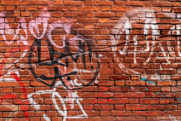 Papiers peints Graffiti red brick wall with graffiti in different colors