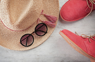 Red shoes, straw hat on wooden background. Sale concept