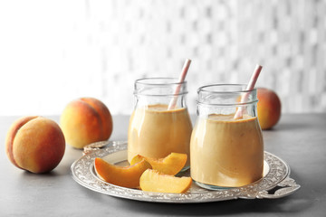 Vintage tray with tasty smoothie and peaches on table
