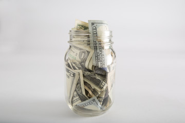 Closeup of Mason jar with money and different dollar amounts