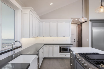 Amazing new contemporary with large white Kitchen with kitchen Island and grey counter tops.