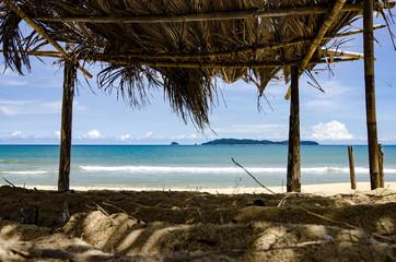 beautiful seaview through bamboo hut. palm fronds, sandy beach a