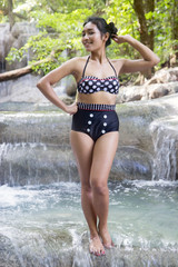 woman in retro swimsuit posing at a water cascade