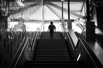 Silhouette of a young man climbing stairs inside interesting architecture